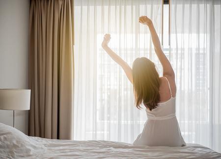 Aziatische vrouw wakker in de ochtend, zittend op witte bed en rekken, gelukkig en fris voelen Stockfoto