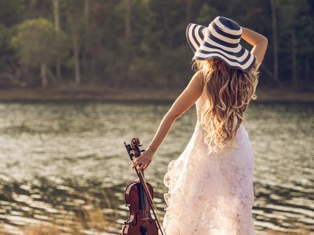 violinista: Músico  violinista de la mujer joven en el vestido blanco que sostiene el violín sobre el río  el parque  el bosque, concepto del tono del vintage de la música del estilo de vida de la libertad.