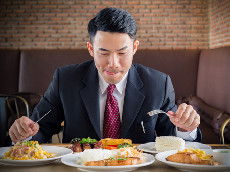 Young asian businessman in formal suit feeling hungry, eating many foods on table at cafe