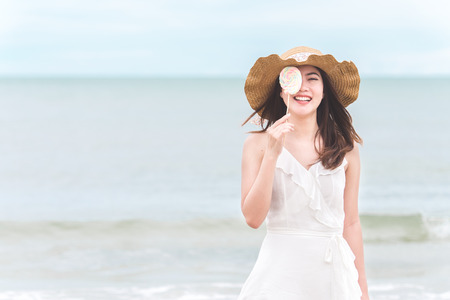 Asian woman on white dress standing over the blue sea and sky, feeling relaxing and happy on vacation in summer holiday
