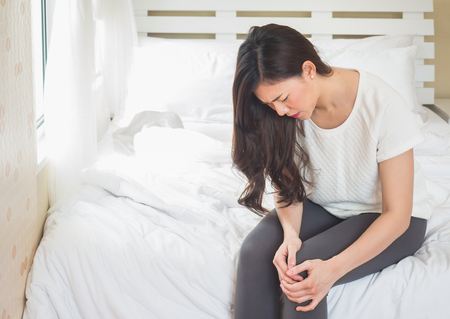 Asiatische Frau, die Knie im Schlafzimmer hält, Frau verletzte Schmerz am Kniekonzept