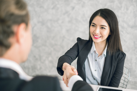 Two of business man and asian business woman shaking hands in the meeting for success and agreement to express teamwork/togetherness and cooperation concept