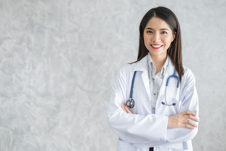 Asian woman doctor with stethoscope in uniform over background with copy space, medical concept