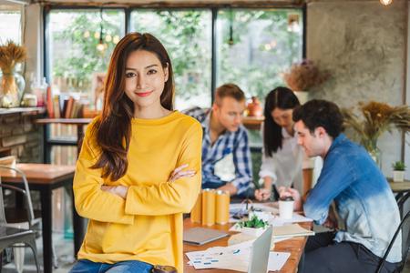 Portret Aziatische zakenvrouw over een groep jong creatief team dat in café werkt Stockfoto