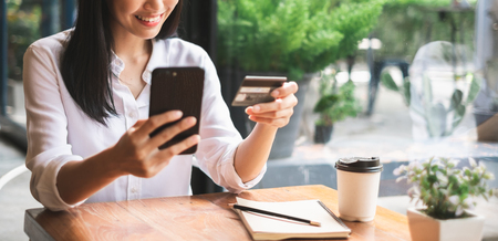 Young beautiful asian woman using smart phone and credit card for shopping online in coffee shop cafe, vintage tone color Imagens