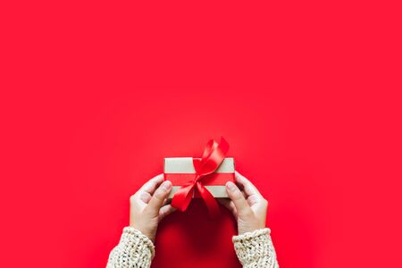 Hand holding gift/presents box over red background for chirstmas and happy new year concept. topview flatlay Stock Photo