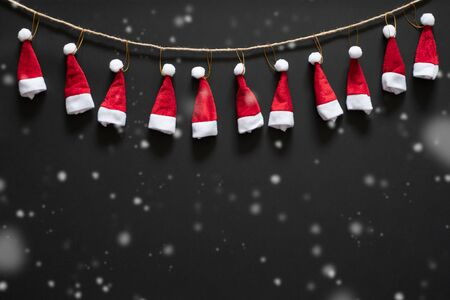 Christmas background with red santa hats and snow over black background and copy space. flatlay