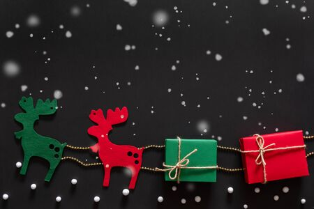 Reindeer carring gift and present box for christmas concept over black background with snow. topview flatlay