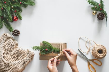 Hand making giftpresents box for christmas concept with decorations over white background and copy space. flatlay