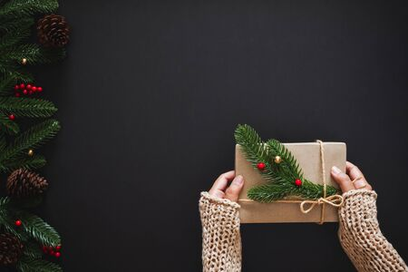 Christmas background with hand holding gift present for christmas and happy new year concept over black background. flatlay topview 스톡 콘텐츠