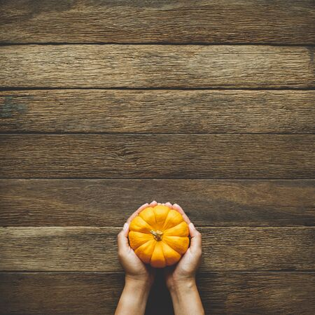 Thanksgiving background, human hand holding pumpkin over wood table background with copy space. flatlay Reklamní fotografie