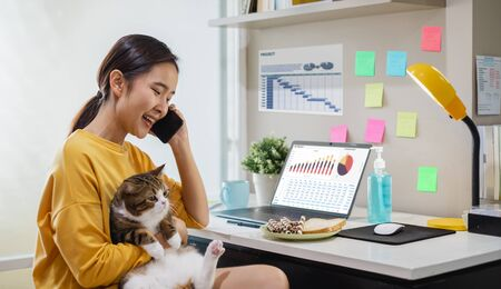 Young Asian woman working from home due to coronavirus covid-19, lifestyle working and playing with her cute cat  , Work from home concept
