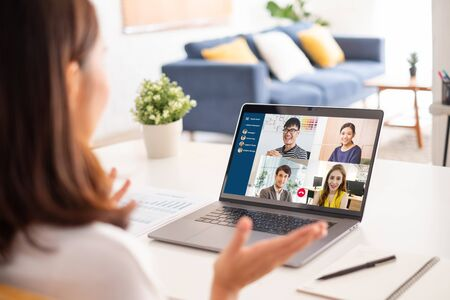 Young Asian businesswoman work at home and virtual video conference meeting with colleagues business people, online working, video call due to social distancing Фото со стока