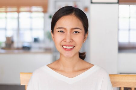 Portrait young Asian businesswoman work at home and virtual video conference meeting with colleagues business people, online working, video call, camera view, front view, look at camera Фото со стока