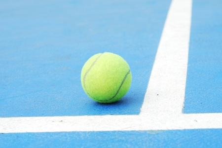 tennis ball on court field at the end line