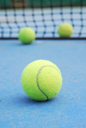 Tennis ball on court with net photo