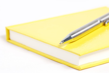 blue pen: silver pen on yellow notebook Stock Photo