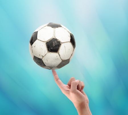 ball point: holding old football with hand on abstract blue background