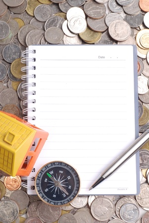 House model and compass with notebook on coins background photo