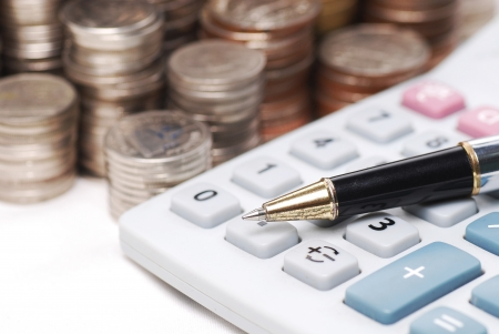 ball pen: Old dusty ball pen on calculator with stack coins background Stock Photo