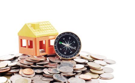 House model and compass on coins background photo