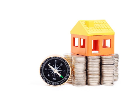 House model on stack of coins and compass Stock Photo - 23197928