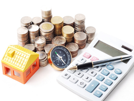 ball pen: model house with stack coins and ball pen on calculator Stock Photo