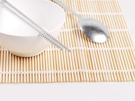 Asian dish place setting on bamboo mat, Korean style photo