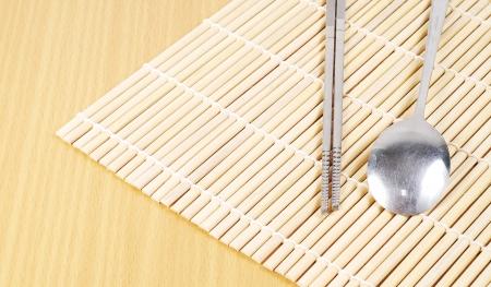 bamboo mat: Asian spoon and chopsticks setting on bamboo mat, Korean style