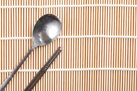 Asian spoon and chopsticks setting on bamboo mat, Korean style photo