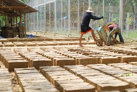 third world economy: Two men making a lot of soil bricks