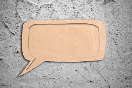 speak bubble: speak bubble with grunge cement wall background Stock Photo