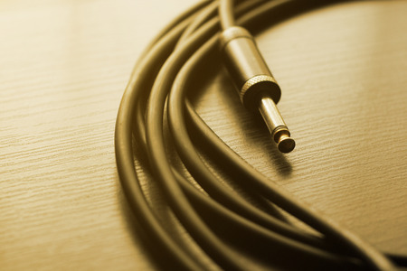 guitar cable audio jack on dark wood background, warm tone Stock Photo