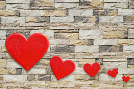 Five hearts on stones wall background Stock Photo