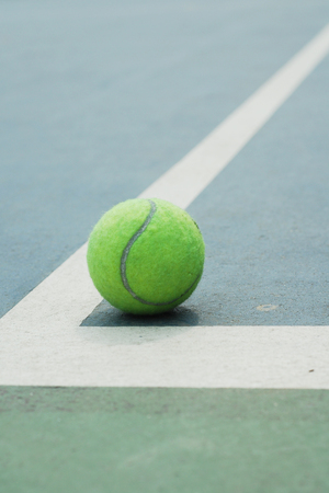 Tennis ball on concrete blue field with white line