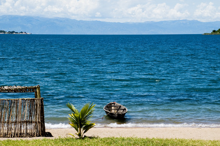 lake: Lonely Boat next to a Shed on the Beach, Lake Tanganyika, Tanzania, Africa Stock Photo
