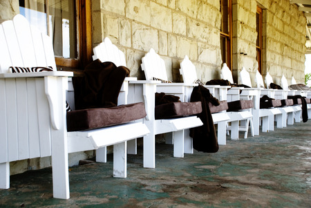 Line of Cozy White Chairs on the Veranda of a Rural Guest House