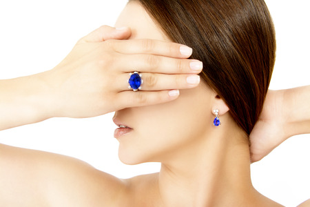 diamond jewellery: Closeup of a Model Wearing a Tanzanite Designer Ring and Earring, Isolated on White