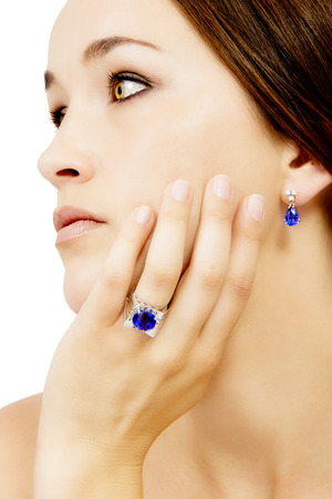 tanzanite: Closeup of a Model Wearing a Tanzanite Designer Ring and Earring, Isolated on White