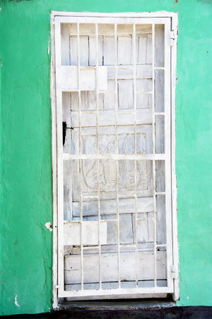 3rd ancient: White door, Turquoise Wall, Black Steps outside House in Urban Residential Area