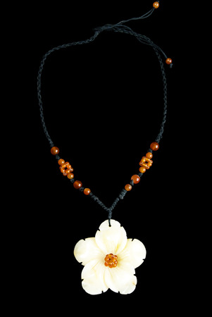 Necklace with Flower and Orange Beads, on Black String, Isolated on Black Background photo