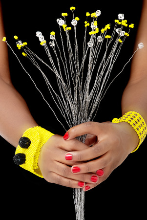 Hands of an African Woman hold White and Yellow Beaded Flowers, with Yellow and Black Bracelets, on Black Background photo