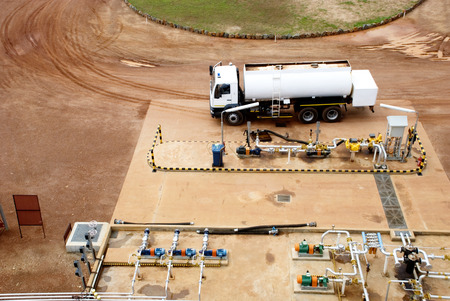 pipe water pipeline: Fuel Truck at Filling Station, Next to Muddy Road