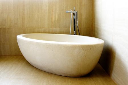 expensive granite: Beautiful Modern Bathtub and Tap in the Corner of Tiled Bathroom Stock Photo