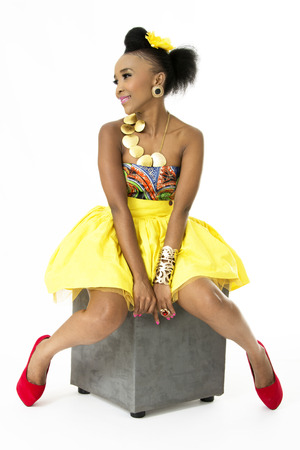 Beautiful African Model Sitting on  Grey Ottoman, Isolated on White