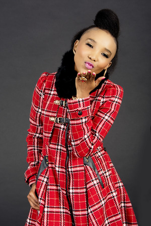 africa kiss: Studio Shot of a Pretty African Fashion Model Blowing a Kiss,  Against a Grey Background Stock Photo