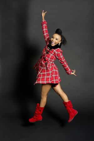 Studio Shot of a Pretty African Fashion Model Jumping, Against a Grey Background
