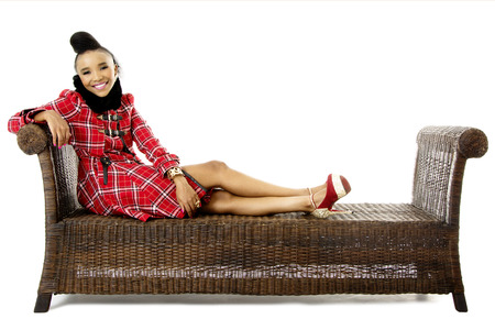 Studio Shot of a Pretty African Fashion Model Relaxing on an Traditional Bench, On White Background Stock Photo