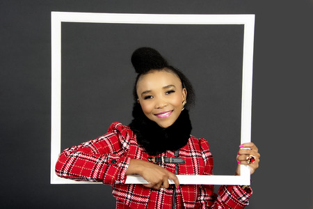 Beautiful African Female Model Holding  a Frame, in the Studio, Grey Background Stock Photo