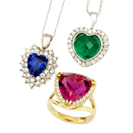 edelstenen: Combinatie van drie Sieraden Pieces: Heart Shaped Sapphire en Diamond Hangend, Heart Shaped Emerald en Diamond Hangend, en een Ruby en Diamond Ring, die op Witte Achtergrond